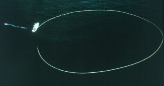1. Positioned in the Pacific Ocean the seine, a large fishing net used in the purse seine fishing technique, is almost a perfect circle. The purse seiner, the ship attached to the net, is starting to pull the net back on board. The workboat (far left) secured to the purse seiner, is now acting like a tugboat, pulling the purse seiner away from the net so that it does not become entangled. Photo Credit: Courtesy of South Pacific Commission (SPC). This photograph is included in the National Oceanic and Atmospheric Administration Photo Library (http://www.photolib.noaa.gov), Fisheries Collection, National Oceanic and Atmospheric Administration (NOAA, http://www.noaa.gov), United States Department of Commerce (http://www.commerce.gov), Government of the United States of America.
