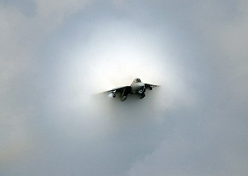 Transonic F-14D Tomcat Fighter Jet With Its Prandtl-Glauert Cloud on July 28, 2006, USS Theodore Roosevelt (CVN 71) Atlantic Ocean. The United States Navy F-14D Tomcat figher jet is 'aircraft number 100, assigned to the Tomcatters of Fighter Squadron Three One (VF-31),' and is making a 'near supersonic fly-by above the flight deck of USS Theodore Roosevelt (CVN 71).' Source for the quotes: 'F-14 near supersonic fly-by' at <http://www.navy.mil/view_single.asp?id=37555>). Photo Credit: Mass Communication Specialist 3rd Class Nathan Laird, Navy NewsStand - Eye on the Fleet Photo Gallery (http://www.news.navy.mil/view_photos.asp, 060728-N-7241L-026), United States Navy (USN, http://www.navy.mil), United States Department of Defense (DoD, http://www.DefenseLink.mil or http://www.dod.gov), Government of the United States of America (USA). This picture (photograph) is included in 'ChamorroBible.org: Prandtl-Glauert Condensation Clouds, 1st Collection', ChamorroBible.org, Manguaguan na Palabran Si Yuus -- God's Precious Words of August 17, 2004.