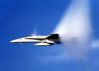 8. An F-18 Hornet From Strike Fighter Squadron 137 (VFA-137), United States Navy, Off the Coast of San Diego, California, USA, Pacific Ocean. Reaching the sound barrier, breaking the sound barrier: Flying at transonic speeds (flying transonically) -- speeds varying near and at the speed of sound (supersonic) -- can generate impressive condensation clouds caused by the Prandtl-Glauert Singularity. For a scientific explanation, see Professor M. S. Cramer's Gallery of Fluid Mechanics, Prandtl-Glauert Singularity at <http://www.GalleryOfFluidMechanics.com/conden/pg_sing.htm>; and Foundations of Fluid Mechanics, Navier-Stokes Equations Potential Flows: Prandtl-Glauert Similarity Laws at <http://www.Navier-Stokes.net/nspfsim.htm>. Photo Credit: Defense Visual Information Center (DVIC, http://www.DoDMedia.osd.mil, DNSD9905858) and United States Navy (USN, http://www.navy.mil), United States Department of Defense (DoD, http://www.DefenseLink.mil or http://www.dod.gov), Government of the United States of America (USA).