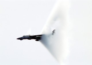 10. An F-14B 'Tomcat' Fighter Jet, April 23, 1999, USS Enterprise (CVN 65), United States Navy Mediterranean Sea. Reaching the sound barrier, breaking the sound barrier: Flying at transonic speeds (flying transonically) -- speeds varying near and at the speed of sound (supersonic) -- can generate impressive condensation clouds caused by the Prandtl-Glauert Singularity. For a scientific explanation, see Professor M. S. Cramer's Gallery of Fluid Mechanics, Prandtl-Glauert Singularity at <http://www.GalleryOfFluidMechanics.com/conden/pg_sing.htm>; and Foundations of Fluid Mechanics, Navier-Stokes Equations Potential Flows: Prandtl-Glauert Similarity Laws at <http://www.Navier-Stokes.net/nspfsim.htm>. Photo Credit: Photographer's Mate Second Class Damon J. Moritz, Image ID: 990423-N-9693M-001, Expeditionary Warfare Division (N75) in the Office of the Chief of Naval Operations, United States Navy (USN, http://www.navy.mil), United States Department of Defense (DoD, http://www.DefenseLink.mil or http://www.dod.gov), Government of the United States of America (USA).