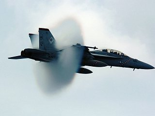 12. An F/A-18F Super Hornet Fighter Assigned to the 'Diamondbacks' of Strike Fighter Squadron One Zero Two (VFA-102). July 27, 2005, USS Kitty Hawk (CV 63), United States Navy in the Philippine Sea. Reaching the sound barrier, breaking the sound barrier: Flying at transonic speeds (flying transonically) -- speeds varying near and at the speed of sound (supersonic) -- can generate impressive condensation clouds caused by the Prandtl-Glauert Singularity. For a scientific explanation, see Professor M. S. Cramer's Gallery of Fluid Mechanics, Prandtl-Glauert Singularity at <http://www.GalleryOfFluidMechanics.com/conden/pg_sing.htm>; and Foundations of Fluid Mechanics, Navier-Stokes Equations Potential Flows: Prandtl-Glauert Similarity Laws at <http://www.Navier-Stokes.net/nspfsim.htm>. Photo Credit: Photographer's Mate 3rd Class Jonathan Chandler, Navy NewsStand - Eye on the Fleet Photo Gallery (http://www.news.navy.mil/view_photos.asp, 050727-N-3488C-051), United States Navy (USN, http://www.navy.mil), United States Department of Defense (DoD, http://www.DefenseLink.mil or http://www.dod.gov), Government of the United States of America (USA).