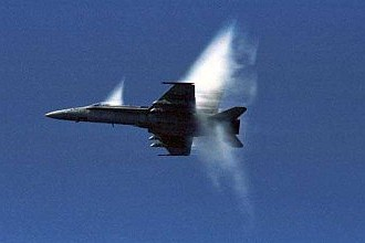 7. An F/A-18 Hornet Fighter Jet, United States Navy, Off the Coast of Nippon-koku (Nihon-koku) - Japan, Sea of Japan. Reaching the sound barrier, breaking the sound barrier: Flying at transonic speeds (flying transonically) -- speeds varying near and at the speed of sound (supersonic) -- can generate impressive condensation clouds caused by the Prandtl-Glauert Singularity. For a scientific explanation, see Professor M. S. Cramer's Gallery of Fluid Mechanics, Prandtl-Glauert Singularity at <http://www.GalleryOfFluidMechanics.com/conden/pg_sing.htm>; and Foundations of Fluid Mechanics, Navier-Stokes Equations Potential Flows: Prandtl-Glauert Similarity Laws at <http://www.Navier-Stokes.net/nspfsim.htm>. Photo Credit: Seventh Fleet - Photos (http://www.c7f.navy.mil/images.html, November 12, Sea of Japan), Commander, U.S. Seventh Fleet (http://www.c7f.navy.mil), United States Navy (USN, http://www.navy.mil), United States Department of Defense (DoD, http://www.DefenseLink.mil or http://www.dod.gov), Government of the United States of America (USA).
