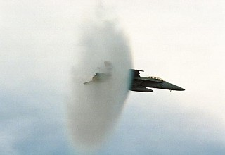 8. An F/A-18E Super Hornet Fighter Jet, United States Navy, Off the Coast of Southern California, United States. Reaching the sound barrier, breaking the sound barrier: Flying at transonic speeds (flying transonically) -- speeds varying near and at the speed of sound (supersonic) -- can generate impressive condensation clouds caused by the Prandtl-Glauert Singularity. For a scientific explanation, see Professor M. S. Cramer's Gallery of Fluid Mechanics, Prandtl-Glauert Singularity at <http://www.GalleryOfFluidMechanics.com/conden/pg_sing.htm>; and Foundations of Fluid Mechanics, Navier-Stokes Equations Potential Flows: Prandtl-Glauert Similarity Laws at <http://www.Navier-Stokes.net/nspfsim.htm>. Photo Credit: PHAA Jeremie Kerns, USS Carl Vinson (CVN 70) Photo Gallery (http://www.vinson.navy.mil/photos/oct00.html, October 2000, 'VFA-122 experts breaking the sound barrier in the F/A 18E at the end of FRS CQs onboard USS Carl Vinson off the coast of southern California.'), USS Carl Vinson (CVN 70) (http://www.vinson.navy.mil), United States Navy (USN, http://www.navy.mil), United States Department of Defense (DoD, http://www.DefenseLink.mil or http://www.dod.gov), Government of the United States of America (USA).