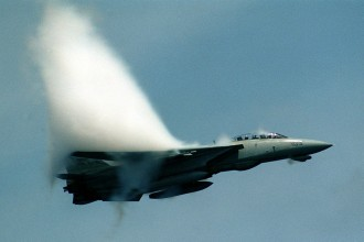 10. An F-14D 'Super Tomcat' Fighter Jet With the Fighter Squadron Two (VF-2), July 10, 1999, USS Constellation (CV 64), United States Navy. Reaching the sound barrier, breaking the sound barrier: Flying at transonic speeds (flying transonically) -- speeds varying near and at the speed of sound (supersonic) -- can generate impressive condensation clouds caused by the Prandtl-Glauert Singularity. For a scientific explanation, see Professor M. S. Cramer's Gallery of Fluid Mechanics, Prandtl-Glauert Singularity at <http://www.GalleryOfFluidMechanics.com/conden/pg_sing.htm>; and Foundations of Fluid Mechanics, Navier-Stokes Equations Potential Flows: Prandtl-Glauert Similarity Laws at <http://www.Navier-Stokes.net/nspfsim.htm>. Photo Credit: Ensign John Gay, Image ID: 990710-N-6483G-001, Expeditionary Warfare Division (N75) in the Office of the Chief of Naval Operations, United States Navy (USN, http://www.navy.mil), United States Department of Defense (DoD, http://www.DefenseLink.mil or http://www.dod.gov), Government of the United States of America (USA).