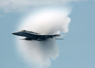 13. An F/A-18C Hornet Fighter Jet Assigned to the 'Golden Dragons' of Strike Fighter Squadron One Nine Two (VFA-192). August 17, 2005, Pacific Ocean. Reaching the sound barrier, breaking the sound barrier: Flying at transonic speeds (flying transonically) -- speeds varying near and at the speed of sound (supersonic) -- can generate impressive condensation clouds caused by the Prandtl-Glauert Singularity. For a scientific explanation, see Professor M. S. Cramer's Gallery of Fluid Mechanics, Prandtl-Glauert Singularity at <http://www.GalleryOfFluidMechanics.com/conden/pg_sing.htm>; and Foundations of Fluid Mechanics, Navier-Stokes Equations Potential Flows: Prandtl-Glauert Similarity Laws at <http://www.Navier-Stokes.net/nspfsim.htm>. Photo Credit: Photographer's Mate 3rd Class Jonathan Chandler, Navy NewsStand - Eye on the Fleet Photo Gallery (http://www.news.navy.mil/view_photos.asp, 050817-N-3488C-151), United States Navy (USN, http://www.navy.mil), United States Department of Defense (DoD, http://www.DefenseLink.mil or http://www.dod.gov), Government of the United States of America (USA). See the companion photo in 'An F/A-18C Hornet conducts a high-speed pass prior to breaking the speed of sound.' at <http://www.news.navy.mil/view_single.asp?id=27228>.