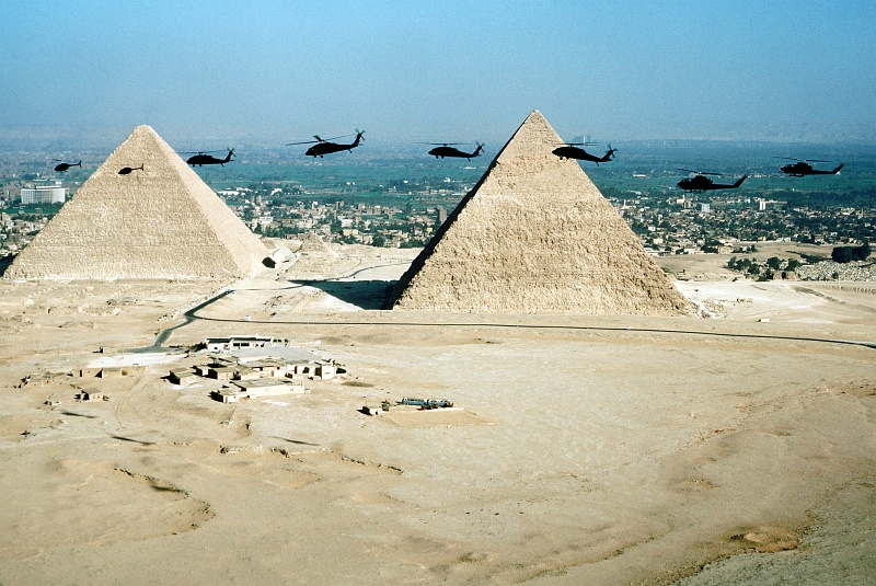 7. Aerial Front-View of West Cairo, Two of The Great Pyramids and, Participating in Exercise Bright Star '80 (From Left-to-Right) 'Two OH-58 Kiowa Helicopters, Four UH-60 Black Hawk Helicopters and Two AH-1 Cobra Helicopters', November 9, 1980, Jumhuriyat Misr al-Arabiyah - Arab Republic of Egypt. Photo Credit: Staff Sgt. Bill Thompson; Defense Visual Information Center (DVIC, http://www.DoDMedia.osd.mil, DF-ST-82-06256), United States Department of Defense (DoD, http://www.DefenseLink.mil or http://www.dod.gov), Government of the United States of America (USA).