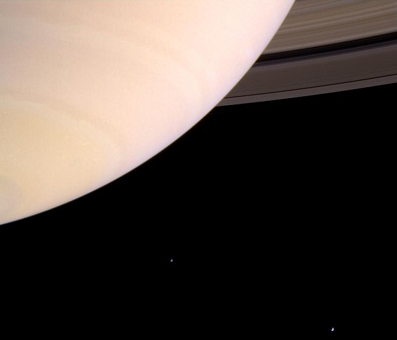 Saturn's Atmosphere, the Rings (upper right), and Two Moons, Mimas and Enceladus (lower right) Photo Credit: Cassini-Huygens Mission (http://saturn.jpl.nasa.gov), Cassini Orbiter, August 8, 2004; National Aeronautics and Space Administration (NASA, http://www.nasa.gov)/Jet Propulsion Laboratory (JPL, http://www.jpl.nasa.gov), Government of the United States of America.