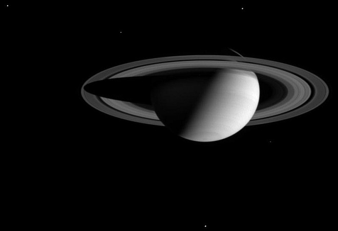Thick Darkness Surrounds Saturn and Five Visible Moons (clockwise from upper left: Dione, Enceladus, Tethys, Mimas, and Rhea). Photo Credit: Cassini-Huygens Mission (http://saturn.jpl.nasa.gov), Cassini Orbiter, August 1, 2004; Planetary Photojournal (http://photojournal.jpl.nasa.gov, PIA06475), National Aeronautics and Space Administration (NASA, http://www.nasa.gov)/Jet Propulsion Laboratory (JPL, http://www.jpl.nasa.gov)/Space Science Institute (http://ciclops.org), Government of the United States of America.