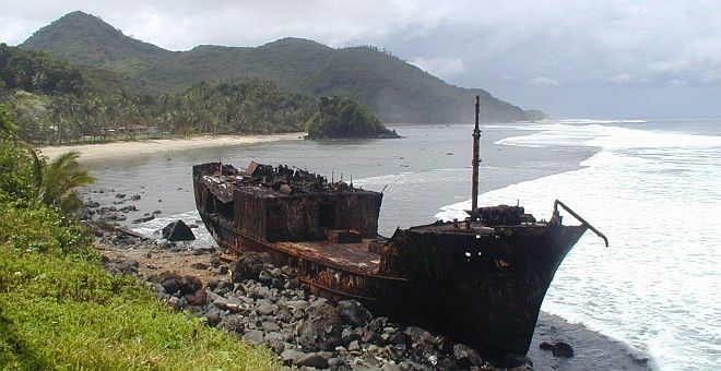 """A Rusted and Broken Ship Thrown Ashore in American Somoa (USA). Photo Credit: """"American Samoa Observatory, Trip to Tula"""", Samoa Observatory Cape Matatula, American Samoa (http://www.cmdl.noaa.gov/obop/smo), Climate Monitoring and Diagnostics Laboratory (http://www.cmdl.noaa.gov), National Oceanic and Atmospheric Administration (NOAA, http://www.noaa.gov), United States Department of Commerce (http://www.commerce.gov), Government of the United States of America (USA)."""