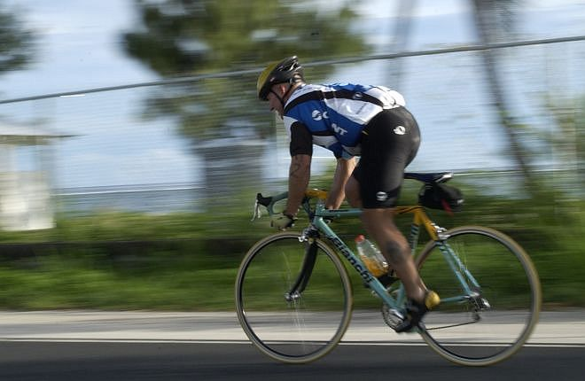 A Cyclist Pedals Hard on His Bicycle in the Guam Triathlon Federation's October 2003 Triathlon, October 12, 2003. Piti, Territory of Guam, USA. Photo Credit: Photographer's Mate 2nd Class Nathanael T. Miller, Navy NewsStand - Eye on the Fleet Photo Gallery (http://www.news.navy.mil/view_photos.asp, 031012-N-7293M-057), United States Navy (USN, http://www.navy.mil), United States Department of Defense (DoD, http://www.DefenseLink.mil or http://www.dod.gov), Government of the United States of America (USA).