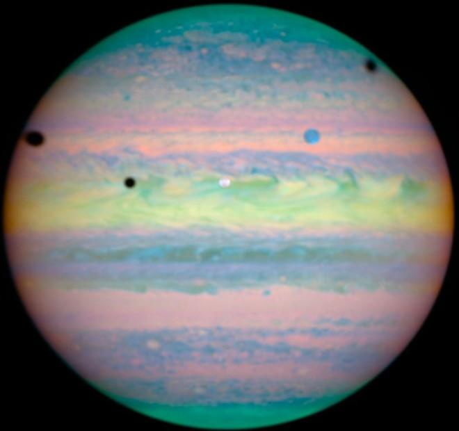 Photographed in Near-infrared Light on March 28, 2004 is a Grand View of Jupiter and a Rare Triple Alignment and Rare Triple Eclipse of Its Three Largest Moons: Io (white circle, center), Ganymede (blue circle, upper right), and Callisto (not shown).  Evidence of This Rare Combination of Celestial Events is Seen by Shadows Cast by the Moons - the Three Black Circles: Io (slightly above center, to the left), Ganymede (left edge), and Callisto (near right edge). Photo Credit: Hubble Spots Rare Triple Eclipse on Jupiter, March 28, 2004 (Release date: November 4, 2004), STScI-2004-30, NASA's Earth-orbiting Hubble Space Telescope; European Space Agency (ESA, http://www.esa.int), Erich Karkoschka (University of Arizona, USA), National Aeronautics and Space Administration (NASA, http://www.nasa.gov), Government of the United States of America (USA).
