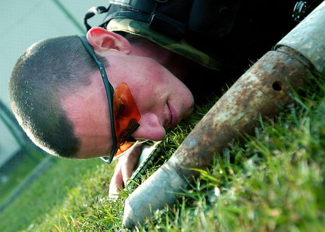 """Patience, Carefulness, and Studiousness are Needed When Working with Dangerous Unxploded Ammunition. Unexploded Ordnance (UXO) Disposal Training at Aviano Air Base, August 24, 2004. Repubblica Italiana - Italian Republic, Photo Credit: Airman 1st Class Scherrie K. Gates, Air Force Link - Photos (http://www.af.mil/photos, 040824-F-5508G-004, """"A sharp eye""""), United States Air Force (USAF, http://www.af.mil), United States Department of Defense (DoD, http://www.DefenseLink.mil or http://www.dod.gov), Government of the United States of America (USA)."""