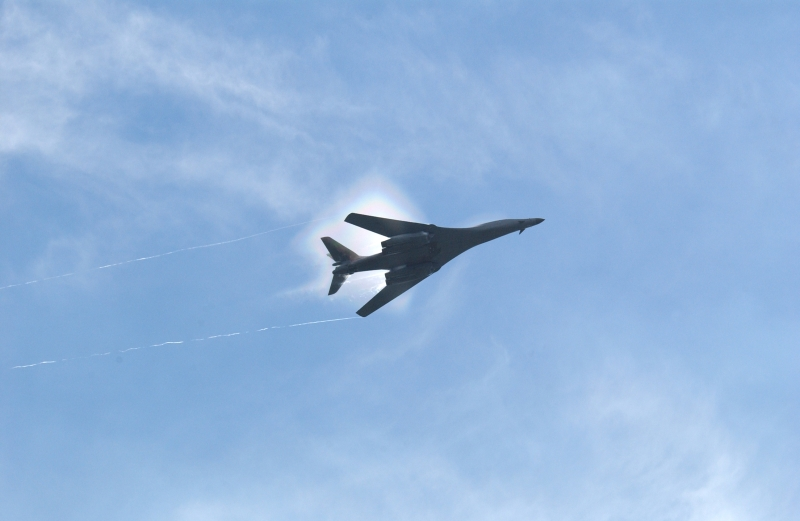 7. A B-1B Lancer Bomber Creating a Prandtl-Glauert Condensation Cloud, United States Air Force. January 16, 2004, Southwest Asia. USAF image ID number: 040116-F-0971G-150. Flying at transonic speeds -- speeds varying near and at the speed of sound (supersonic) -- can generate impressive condensation clouds caused by the Prandtl-Glauert Singularity. For a scientific explanation, see Dr. Mark. S. Cramer's Gallery of Fluid Mechanics, Prandtl-Glauert Singularity at <http://www.GalleryOfFluidMechanics.com/conden/pg_sing.htm>; the Prandtl-Glauert Condensation Clouds tutorial at <http://FluidMech.net/tutorials/sonic/prandtl-glauert-clouds.htm>; and Foundations of Fluid Mechanics, Navier-Stokes Equations Potential Flows: Prandtl-Glauert Similarity Laws at <http://www.Navier-Stokes.net/nspfsim.htm>. Photo Credit: Staff Sgt. Shelley Gill, Still Photography Journeyman, 125th Fighter Wing, Florida Air National Guard, USA; 040116-F-0971G-150, United States Air Force (USAF, http://www.af.mil), United States Department of Defense (DoD, http://www.DefenseLink.mil or http://www.dod.gov), Government of the United States of America (USA).
