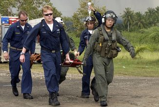 Carrying a Tsunami Victim to a Triage Site Located on Sultan Iskandar Muda Air Force Base, January 8, 2005. Banda Aceh, Sumatra, Republik Indonesia. Photo Credit: Photographer's Mate 3rd Class Katrina V. Walter, Navy NewsStand - Eye on the Fleet Photo Gallery (http://www.news.navy.mil/view_photos.asp, 050108-N-6736W-012), United States Navy (USN, http://www.navy.mil), United States Department of Defense (DoD, http://www.DefenseLink.mil or http://www.dod.gov), Government of the United States of America (USA). This photograph is included in ChamorroBible.org: The Great Earthquake and Catastrophic Tsunami of 2004, Part 4.