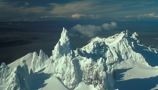 The Lofty Aghileen Pinnacles (foreground), in the Background, Frosty, Roundtop, Isanotski and Shishaldin. Izembek National Wildlife Refuge, State of Alaska, USAPhoto Credit: John Sarvis, Alaska Historical Image Library, United States Fish and Wildlife Service Digital Library System (http://images.fws.gov, AK/RO/03146), United States Fish and Wildlife Service (FWS, http://www.fws.gov), United States Department of the Interior (http://www.doi.gov), Government of the United States of America (USA).