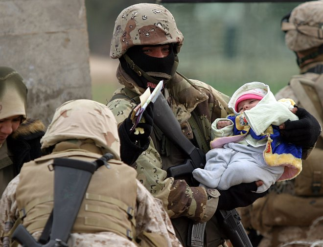 This Bundled-Up Colorfully-Dressed Baby, Nestled in a Soldier's Protective Arms and Surrounded by Soldiers, Rests Without Worry, January 30, 2005. Nasarwasalam, Al Jumhuriyah al Iraqiyah - Republic of Iraq. Photo Credit: Cpl. Trevor Gift of the United States Marine Corps (USMC, http://www.usmc.mil), Navy NewsStand - Eye on the Fleet Photo Gallery (http://www.news.navy.mil/view_photos.asp, 050130-M-7981G-034), United States Navy (USN, http://www.navy.mil); United States Department of Defense (DoD, http://www.DefenseLink.mil or http://www.dod.gov), Government of the United States of America (USA).