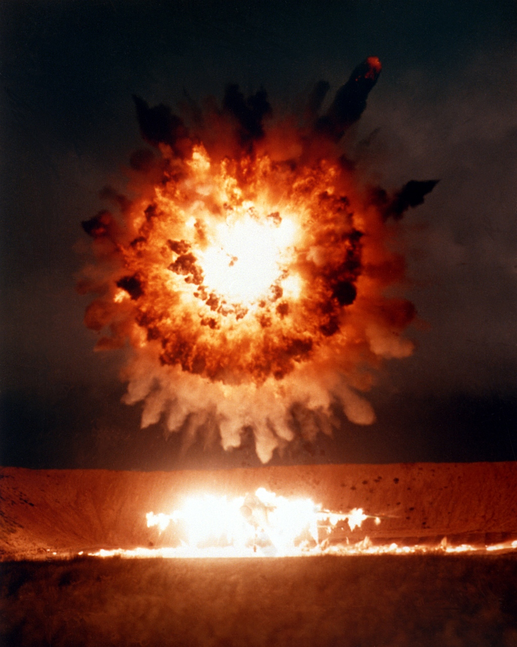 6. The BGM-109 Tomahawk Cruise Missile's 1,000-Pound Conventional Warhead Explodes Over the Revetted Aircraft, April 1, 1986, San Clemente Island, State of California, USA. Photo Credit: Defense Visual Information Center (DVIC, http://www.DoDMedia.osd.mil, DN-SC-86-06115) and United States Navy (USN, http://www.navy.mil), United States Department of Defense (DoD, http://www.DefenseLink.mil or http://www.dod.gov), Government of the United States of America (USA).