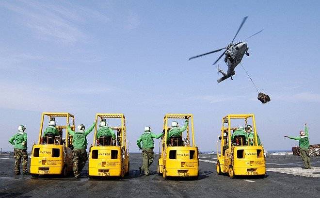 USS Abraham Lincoln (CVN 72) Sailors With Their Forklifts Wait for the MH-60S Knighthawk Helicopter to Deliver Supplies for Operation Unified Assistance, the International Humanitarian Relief Operation Triggered by The Great Earthquake and Catastrophic Tsunami of 2004 <http://ChamorroBible.org/gpw/gpw-The-Great-Earthquake-and-Catastrophic-Tsunami-of-2004.htm>. January 21, 2005, In the Indian Ocean Near the Kingdom of Thailand and Republik Indonesia. Photo Credit: Photographer's Mate Airman Jordon R. Beesley, Navy NewsStand - Eye on the Fleet Photo Gallery (http://www.news.navy.mil/view_photos.asp, 050121-N-4166B-025), United States Navy (USN, http://www.navy.mil), United States Department of Defense (DoD, http://www.DefenseLink.mil or http://www.dod.gov), Government of the United States of America (USA).