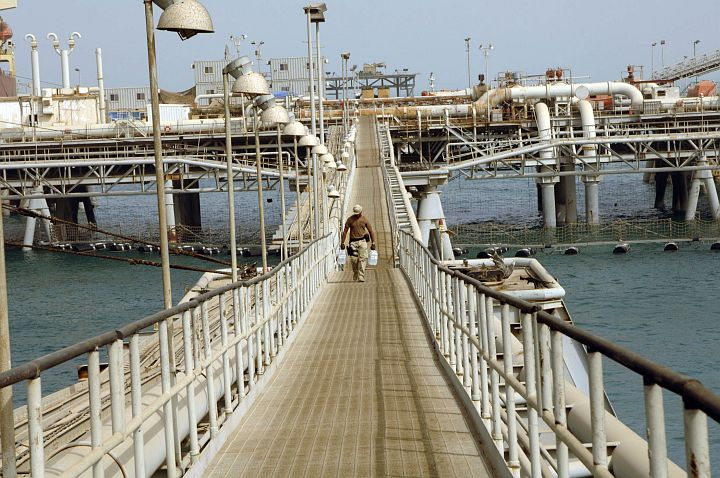Walking Alone On Bridge (or Walkway) That Spans a Portion of the North Persian Gulf's Flowing Waters to Bring Needed Bottled Water (H20), June 12, 2005. Al Basrah Oil Terminal, Basra, Al Jumhuriyah al Iraqiyah - Republic of Iraq. Photo Credit: Photographer's Mate 1st Class Aaron Ansarov, Navy NewsStand - Eye on the Fleet Photo Gallery (http://www.news.navy.mil/view_photos.asp, 050612-N-4309A-350), United States Navy (USN, http://www.navy.mil); United States Department of Defense (DoD, http://www.DefenseLink.mil or http://www.dod.gov), Government of the United States of America (USA).