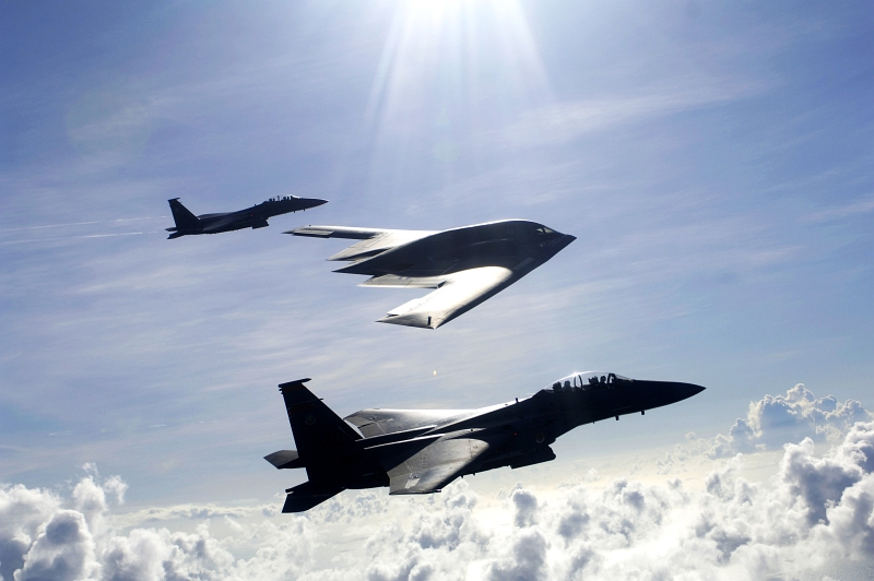 17. A U.S. Air Force (USAF) B-2 Spirit Stealth Bomber and Two USAF F-15E Strike Eagle Fighter Jets Fly High Above the Clouds Over the Pacific Ocean, July 7, 2005, Andersen Air Force Base, Territory of Guam, USA. Photo Credit: Tech. Sgt. Cecilio Ricardo, United States Air Force (USAF, http://www.af.mil); Defense.gov News Photos (http://www.Defense.gov/photos/, 050707-F-3961R-002), United States Department of Defense (DoD, http://www.Defense.gov or http://www.dod.gov), Government of the United States of America (USA).
