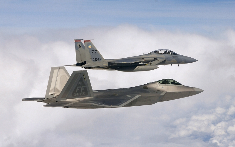 19. A USAF F-22A Raptor Stealth Fighter Jet Flies In Formation With A F-15 Eagle Fighter Jet, October 18, 2007, Off the Coast of the State of North Carolina, USA. The F-15 Eagle (top) is piloted by USAF Capt. Bradley Brumbaugh (71st Fighter Squadron) with Bill Weir (a co-anchor for ABC's 'Good Morning America' show) in the back seat. The USAF F-22A Raptor (bottom) is piloted by USAF Capt. Greg Priesser (94th Fighter Squadron). Photo Credit: Staff Sgt. Samuel Rogers, United States Air Force; Defense Visual Information (DVI, http://www.DefenseImagery.mil, 071018-F-WB275-055) and United States Air Force (USAF, http://www.af.mil), United States Department of Defense (DoD, http://www.DefenseLink.mil or http://www.dod.gov), Government of the United States of America (USA).