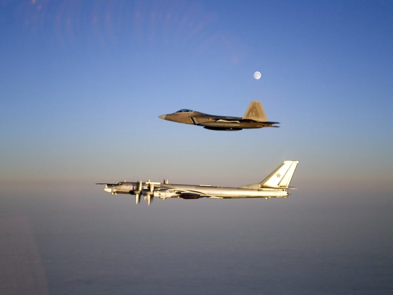 "12. A U.S. Air Force F-22A Raptor Stealth Fighter Jet Intercepting and Escorting A Russian Tu-95MS Strategic Heavy Bomber Under A Full Moon, November 22, 2007, Near Alaskan NORAD Region Airspace. Photo Credit: United States Air Force; AF.mil - Photos (http://www.af.mil/photos, 071122-F-1234X-001, ""ANR [Alaskan North American Aerospace Defense Command (NORAD) Region] celebrates 50 years protecting Alaskan skies""), United States Department of Defense (DoD, http://www.DefenseLink.mil or http://www.dod.gov), Government of the United States of America (USA). Additional details from the USAF: Two F-22 Raptors from 11th Air Force, 3rd Wing, based at Elmendorf Air Force Base, Alaska intercepted a pair of Russian Tu-95MS strategic bombers on November 22, 2007. Both ""Bears"" belong to the 326th Heavy Bomber Air Division and are operated from Ukrainka air base. The intercept was a first for the Raptor."