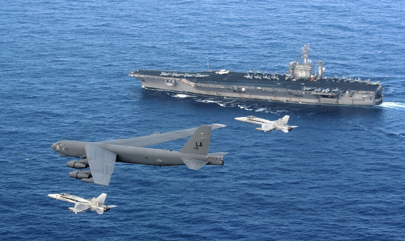 5. Two U.S. Navy F/A-18 Hornet Fighter Jets Intercept the Low-Flying U.S. Air Force B-52 Stratofortress Heavy Bomber As the Bomber Performs A Rigging Maneuver to Identify the Aircraft Carrier USS Nimitz (CVN 68), April 23, 2008. Photo Credit: Tech. Sgt. Corey Clements, United States Air Force; Defense Visual Information (DVI, http://www.DefenseImagery.mil, 080423-F-OJ435-003) and United States Air Force (USAF, http://www.af.mil), United States Department of Defense (DoD, http://www.DefenseLink.mil or http://www.dod.gov), Government of the United States of America (USA).