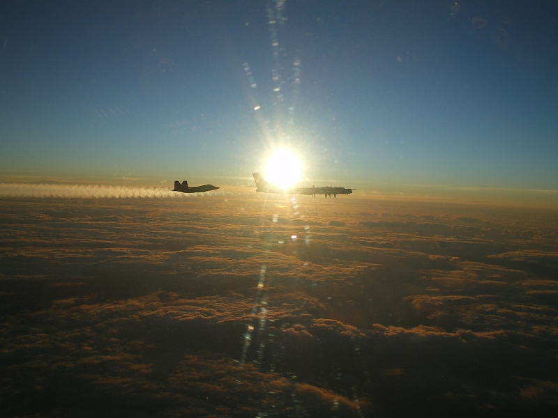 "10. Backdropped by the Bright Sun, A U.S. Air Force F-22A Raptor Stealth Fighter Jet Intercepts and Escorts A Russian Tu-95MS Strategic Heavy Bomber, November 22, 2007, Near Alaskan NORAD Region Airspace. Photo Credit: United States Air Force; Pacific Air Forces - Photos (http://www.pacaf.af.mil/photos, 081010-F-1234X-019, ""F-22 Raptor intercepts Russian bomber""), United States Department of Defense (DoD, http://www.DefenseLink.mil or http://www.dod.gov), Government of the United States of America (USA). Additional information from the USAF: Two F-22 Raptors from 11th Air Force, 3rd Wing, based at Elmendorf Air Force Base, Alaska intercepted a pair of Russian Tu-95MS strategic bombers on November 22, 2007. Both ""Bears"" belong to the 326th Heavy Bomber Air Division and are operated from Ukrainka air base. The intercept was a first for the Raptor."