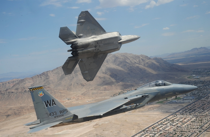 13. A U.S. Air Force F-22A Raptor Stealth Fighter Jet Peels Away From A U.S. Air Force F-15 Eagle Fighter Jet To Land At Nellis Air Force Base, July 16, 2010, State of Nevada, USA. Photo Credit: Master Sgt. Kevin J. Gruenwald, United States Air Force; Defense Visual Information (DVI, http://www.DefenseImagery.mil, 100716-F-6911G-592) and United States Air Force (USAF, http://www.af.mil), United States Department of Defense (DoD, http://www.DefenseLink.mil or http://www.dod.gov), Government of the United States of America (USA).