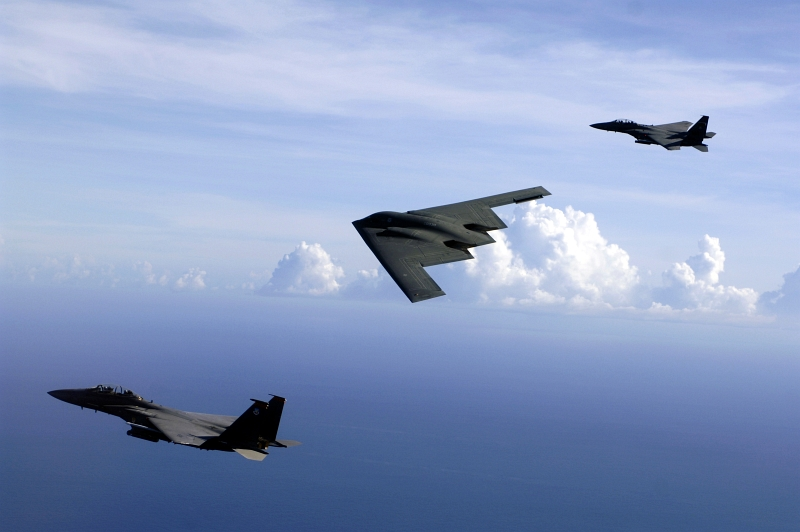8. Two U.S. Air Force F-15E Strike Eagle Fighter Jets and A U.S. Air Force B-2 Spirit Stealth Bomber Flying In Formation Over the Pacific Ocean, July 5, 2005, Andersen Air Force Base, Territory of Guam, USA. Photo Credit: Technical Sgt. (TSgt) Cecilio M. Ricardo, United States Air Force; Defense Visual Information (DVI, http://www.DefenseImagery.mil, DF-SD-08-19939 or 050705-F-3961R-402) and United States Air Force (USAF, http://www.af.mil), United States Department of Defense (DoD, http://www.DefenseLink.mil or http://www.dod.gov), Government of the United States of America (USA).