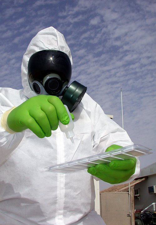 "On Guard for Death and Disease in the Air: Dressed in Protective Clothing With a Biological or Chemical Agent Testing Kit in Southwest Asia. Photo Credit: Master Sgt. Michael A. Ward, Air Force Link - Week in Photos, February 25, 2005 (http://www.af.mil/weekinphotos/050225-08.html, ""Not your old disaster prepardeness anymore""), United States Air Force (USAF, http://www.af.mil), United States Department of Defense (DoD, http://www.DefenseLink.mil or http://www.dod.gov), Government of the United States of America (USA)."