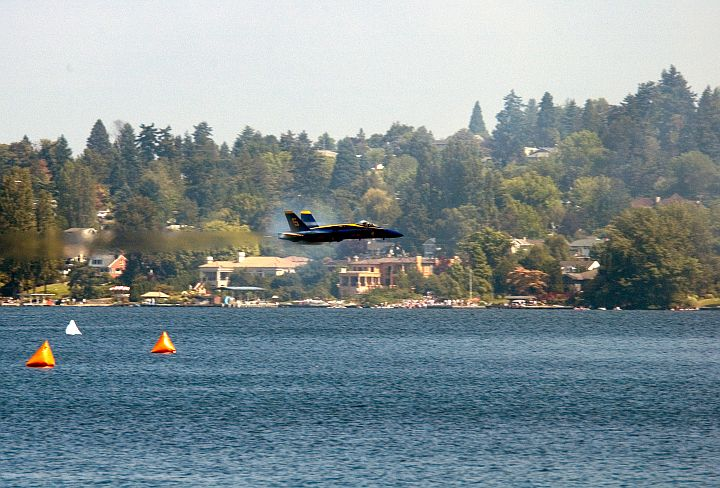 August 6, 2005, SEAFAIR 2005 KeyBank Air Show, Seattle, State of Washington, USA: The Scenic View of the Tree-Covered Landscape Overlooking Lake Washington is Enhanced by the Prandtl-Glauert Cloud Around a Low Flying and Transonic U.S. Navy Blue Angels F/A-18A Hornet Fighter Jet. Photo Credit: Photographer's Mate 3rd Class Douglas G. Morrison, Navy NewsStand - Eye on the Fleet Photo Gallery (http://www.news.navy.mil/view_photos.asp, 050806-N-3390M-019), United States Navy (USN, http://www.navy.mil), United States Department of Defense (DoD, http://www.DefenseLink.mil or http://www.dod.gov), Government of the United States of America (USA). Flying within the transonic regime -- speeds varying near and at the speed of sound (supersonic) -- can generate impressive condensation clouds caused by the Prandtl-Glauert Singularity. For a scientific explanation, see Dr. Mark. S. Cramer's Gallery of Fluid Mechanics, Prandtl-Glauert Singularity at <http://www.GalleryOfFluidMechanics.com/conden/pg_sing.htm>; the Prandtl-Glauert Condensation Clouds tutorial at <http://FluidMech.net/tutorials/sonic/prandtl-glauert-clouds.htm>; and Foundations of Fluid Mechanics, Navier-Stokes Equations Potential Flows: Prandtl-Glauert Similarity Laws at <http://www.Navier-Stokes.net/nspfsim.htm>.