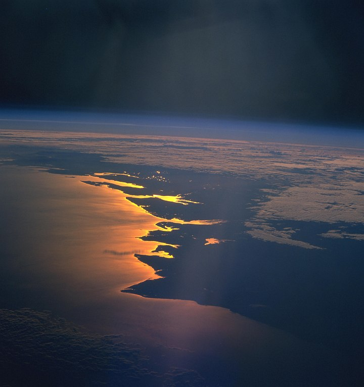 Space Shuttle Columbia (STS-93), July 26, 1999, 03:40:43 UTC: Planet Earth's Beautiful Sunrise -- Reflected Light In Glowing Shades of Gold, Yellow and Orange -- on the Mozambique Channel Along the Coast of Republique de Madagascar - Republic of Madagascar. Photo Credit: NASA's Space Shuttle Columbia: STS-93 Mission; NASA-Johnson Space Center. 'Astronaut Photography of Earth - Display Record.' <http://eol.jsc.nasa.gov/scripts/sseop/photo.pl?mission=STS093&roll=716&frame=65>; National Aeronautics and Space Administration (NASA, http://www.nasa.gov), Government of the United States of America (USA). The photo's full size request URL is <http://eol.jsc.nasa.gov/scripts/sseop/LargeImageAccess.pl?directory=ISD/highres/STS093&filename=STS093-716-65_4.JPG&filesize=1341594>