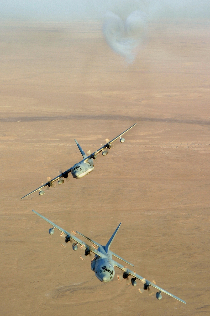4. Aerial View of Two United States Marine Corps KC-130 Hercules Aircraft, Assigned to Marine Aerial Refueler-Transport Squadron Two Thirty Four (VMGR-234), Executing Trial Evasive Maneuvers After Firing Flares Used to Counter an Attack by Surface to Air Missiles (SAMs or SAM) During Operation Iraqi Freedom, September 4, 2003, Al Jumhuriyah al Iraqiyah - Republic of Iraq. Photo Credit: Lance Cpl. Andrew Z. Williams, United States Marine Corps (USMC, http://www.usmc.mil); Defense Visual Information Center (DVIC, http://www.DoDMedia.osd.mil, DMSD0511419 and 030904M7837W012) and United States Marine Corps (USMC, http://www.usmc.mil), United States Department of Defense (DoD, http://www.DefenseLink.mil or http://www.dod.gov), Government of the United States of America (USA).
