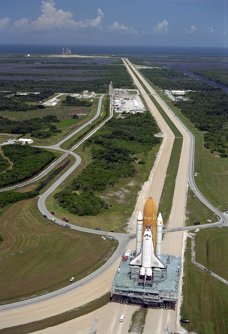 10. Scenic View of the Area Surrounding Space Shuttle Atlantis (STS-79), Atop the Mobile Launcher Platform (MLP) and Crawler-Transporter, As It Slowly Rolls Out to Launch Pad 39A on Merrit Island, August 20, 1996, NASA John F. Kennedy Space Center, State of Florida, USA. Photo Credit: NASA; Rollout of Space Shuttle Atlantis (STS-79) to Launch Pad 39A, GRIN (http://grin.hq.nasa.gov) Database Number: GPN-2000-000967, National Aeronautics and Space Administration (NASA, http://www.nasa.gov), Government of the United States of America.