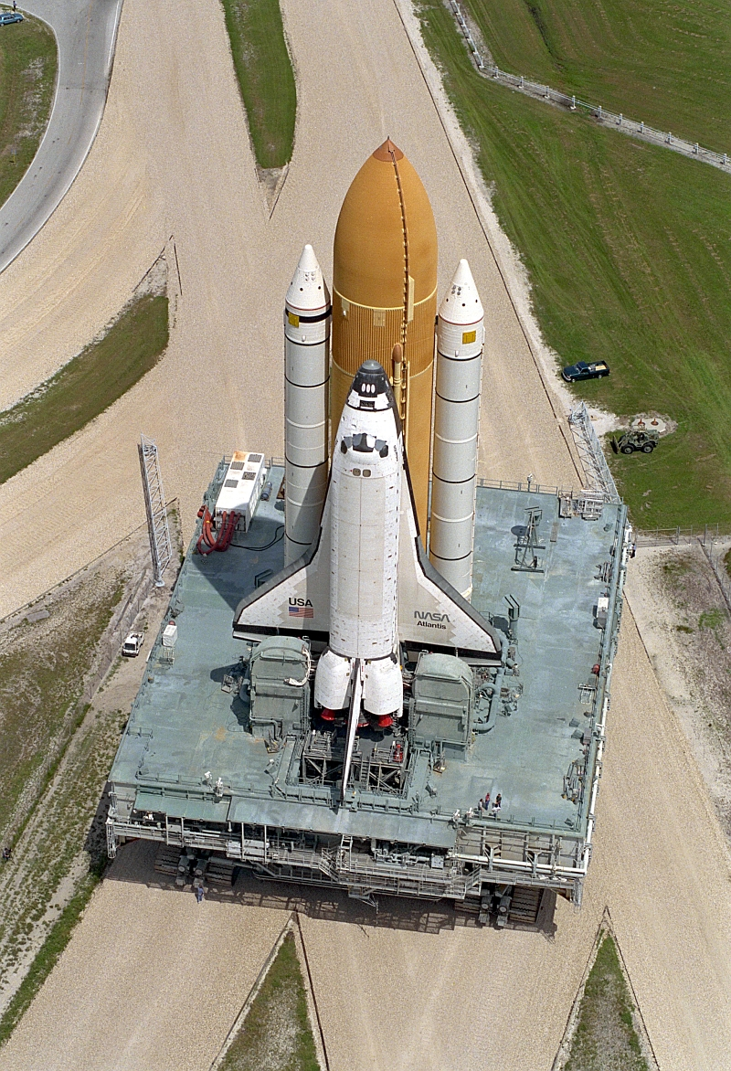 9. Atop the Mobile Launcher Platform (MLP) and Crawler-Transporter, Space Shuttle Atlantis (STS-79) Rolls Out to Launch Pad 39A, August 20, 1996, NASA John F. Kennedy Space Center, State of Florida, USA. Photo Credit: NASA; Rollout of Space Shuttle Atlantis (STS-79) to Launch Pad 39A, GRIN (http://grin.hq.nasa.gov) Database Number: GPN-2000-000968, National Aeronautics and Space Administration (NASA, http://www.nasa.gov), Government of the United States of America.