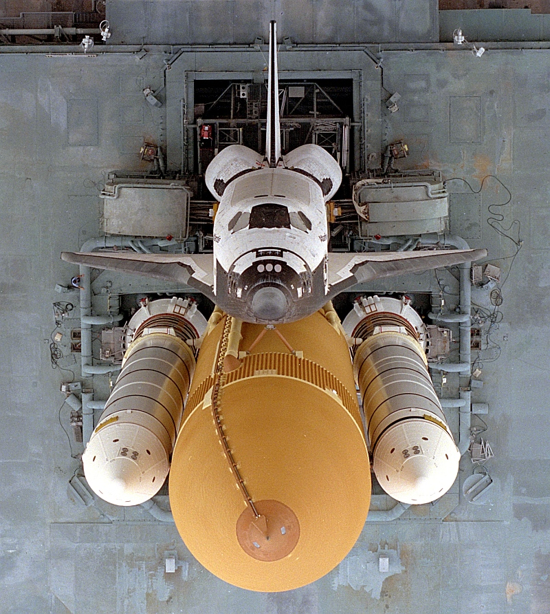 3. Looking Directly Down at Space Shuttle Atlantis (STS-79) Atop the Mobile Launcher Platform (MLP) and Crawler-Transporter From 525 Feet (160 Meters) Above the Ground, August 20, 1996. NASA John F. Kennedy Space Center, State of Florida, USA. Photo Credit: NASA; Overhead view of Space Shuttle Atlantis (STS-79) stack rollout, GRIN (http://grin.hq.nasa.gov) Database Number: GPN-2000-001877, National Aeronautics and Space Administration (NASA, http://www.nasa.gov), Government of the United States of America.