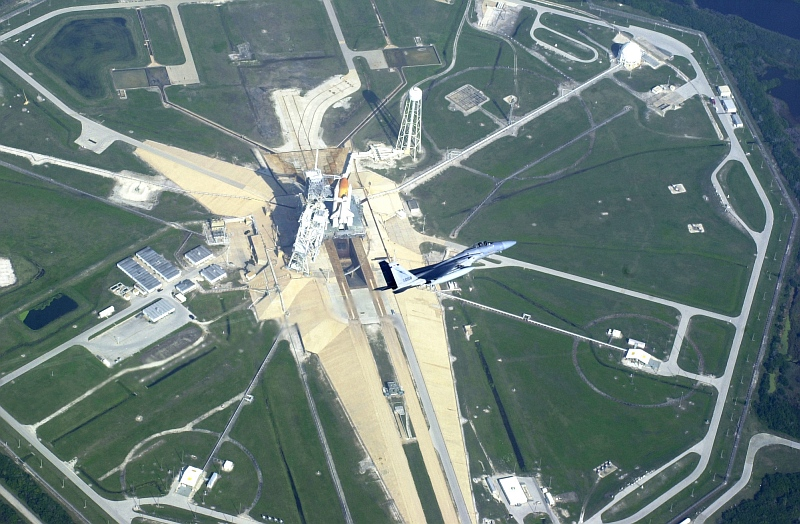 2. Operation Noble Eagle: Aerial View of a Florida Air National Guard F-15C Eagle Fighter Jet, Assigned to the 125th Fighter Wing, Flying a Combat Air Patrol (CAP) Mission Over Cape Kennedy As Space Shuttle Endeavour (STS-108) Sits On Launch Pad 39B, November 29, 2001, NASA John F. Kennedy Space Center, State of Florida, USA. Photo Credit: Tech. Sgt. (TSgt.) Shaun Withers, United States Air Force (USAF, http://www.af.mil); Defense Visual Information Center (DVIC, http://www.DoDMedia.osd.mil, DF-SD-03-17847 and 011129-F-1279W-025) and United States Air Force (USAF, http://www.af.mil), United States Department of Defense (DoD, http://www.DefenseLink.mil or http://www.dod.gov), Government of the United States of America (USA).