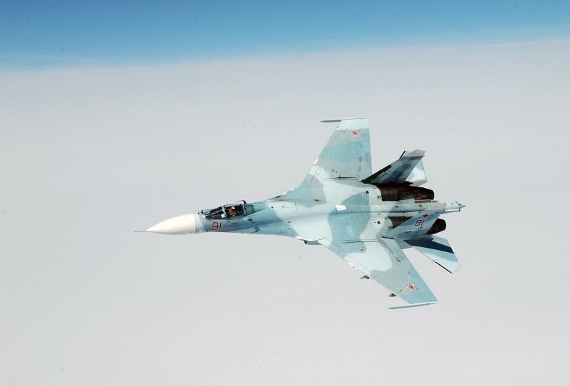 26. Joint NORAD-Russia Exercise VIGILANT EAGLE: High Above the Pacific Ocean, One Russian Federation Air Force Su-27 Fighter Jet Moves Into Position to Escort an Airliner During the International Hijacking Senario, August 9, 2011. Photo Credit: Tech. Sgt. Thomas J. Doscher, United States Air Force; North American Aerospace Defense Command (NORAD, http://www.norad.mil, 110809-F-YX459-482), United States Department of Defense (DoD, http://www.DefenseLink.mil or http://www.dod.gov), Government of the United States of America (USA).