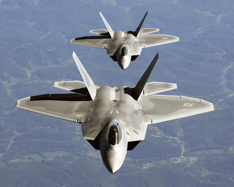 19. Two U.S. Air Force F-22A Raptor Stealth Fighter Jets, In Trailing Formation, Fly To Hill Air Force Base, Utah, For Exercise Combat Hammer, October 15, 2005. Photo Credit: Tech. Sgt. Ben Bloker, United States Air Force; Defense Visual Information (DVI, http://www.DefenseImagery.mil, DF-SD-08-17711 and 051015-F-2295B-043) and United States Air Force (USAF, http://www.af.mil), United States Department of Defense (DoD, http://www.DefenseLink.mil or http://www.dod.gov), Government of the United States of America (USA).