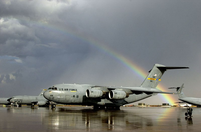 """A Beautiful, Partially Very Bright Rainbow -- an Arc of Light -- Effortlessly Cuts Through a Dark Sky Full of Grey Clouds After a Sudden and Heavy Rain Shower, Arching Over the Airfield at Moron Air Base, January 2003, Reino de España - Kingdom of Spain. Photo Credit: Staff Sgt. P. J. Farlin, Air Force Link - Photos (http://www.af.mil/photos, 030128-O-9999J-023, """"Rainbow After Rain""""), United States Air Force (USAF, http://www.af.mil), United States Department of Defense (DoD, http://www.DefenseLink.mil or http://www.dod.gov), Government of the United States of America (USA)."""