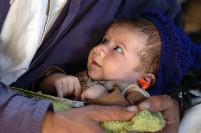 This Pakistani child -- with a red earplug in his ear for noise protection -- is safe and secure on the lap and in the arms and hands of his father, as his parents are airlifted by helicopter to a medical treatment facility. The city of Muzafarabad was devastated by an earthquake that shook the region on October 8th, 2005. Aboard a United States Navy MH-53E Sea Stallion helicopter assigned to Helicopter Mine Countermeasure Squadron Fifteen (HM-15), October 14, 2005, Muzafarabad, Islamic Republic of Pakistan. Photo Credit: Photographer's Mate 2nd Class Timothy Smith, Navy NewsStand - Eye on the Fleet Photo Gallery (http://www.news.navy.mil/view_photos.asp, 051014-N-8796S-046), United States Navy (USN, http://www.navy.mil), United States Department of Defense (DoD, http://www.DefenseLink.mil or http://www.dod.gov), Government of the United States of America (USA).