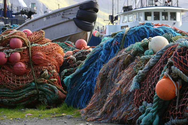 Docked Ships and a Very Colorful Pile of Fishing Nets at Dutch Harbor, Alaska Maritime National Wildlife Refuge, Unalaska, Aleutian Islands, State of Alaska, USA. Photo Credit: Carla Stanley, Alaska Image Library, United States Fish and Wildlife Service Digital Library System (http://images.fws.gov), United States Fish and Wildlife Service (FWS, http://www.fws.gov), United States Department of the Interior (http://www.doi.gov), Government of the United States of America (USA).