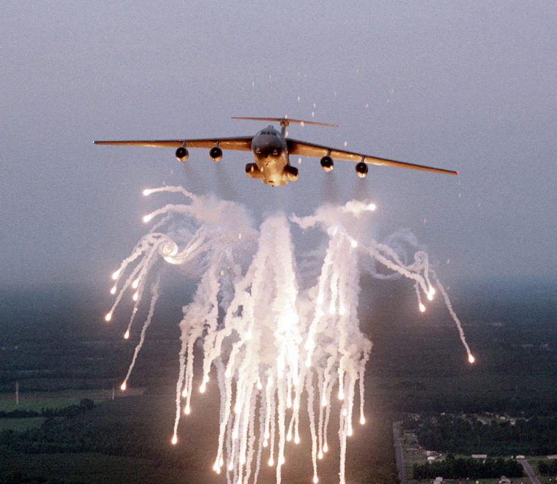 "1. Flares and smoke from the flare salvo -- fired by an overland United States Air Force C-141B Starlifter Cargo and Troop Transport, a jet-powered airlifter -- leaves in the sky a bright, dazzling-to-the-eye, white, spectacular formation with glowing ""tips"" that are very hot. The well-defined vortex on the left is caused by air turbulence created by the flight of the C-141B StarLifter aircraft. The flare countermeasure, a self-defense decoy operation or technique, is used to help protect the aircraft from an attack (or attacks) by deadly heat-seeking missiles. Photo Credit: Senior Airman Greg Davis, Air Force Link - Photos (http://www.af.mil/photos, 021205-O-9999G-017, ""Fireworks display""), United States Air Force (USAF, http://www.af.mil), United States Department of Defense (DoD, http://www.DefenseLink.mil or http://www.dod.gov), Government of the United States of America (USA)."