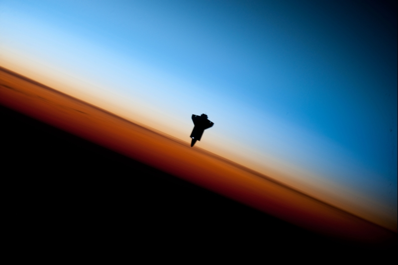 36. Orbital Sunset: Silhouette of Space Shuttle Endeavour (STS-130) and Earth's Colorful Horizon, February 9, 2010, As Seen From the International Space Station (Expedition Twenty-Two) While Orbiting Above the South Pacific Ocean Off the Coast of Southern Chile, South America: Latitude (LAT): -46.9, Longitude (LON): -80.5, Altitude (ALT): 183 Nautical Miles. Photo Credit: STS-130 Shuttle Mission Imagery (http://spaceflight.nasa.gov/gallery/images/shuttle/sts-130/ndxpage1.html), ISS022-E-062673 (http://spaceflight.nasa.gov/gallery/images/shuttle/sts-130/html/iss022e062673.html), NASA Human Space Flight (http://spaceflight.nasa.gov), National Aeronautics and Space Administration (NASA, http://www.nasa.gov), Government of the United States of America. Additional information from NASA: 'The orange layer is the troposphere, where all of the weather and clouds which we typically watch and experience are generated and contained. This orange layer gives way to the whitish Stratosphere and then into the Mesosphere. In some frames the black color is part of a window frame rather than the blackness of space.'