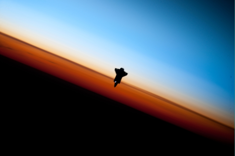 37. Orbital Sunset: Striking View of Earth's Colorful Horizon and the Silhouette of Space Shuttle Endeavour (STS-130), February 9, 2010, As Seen From the International Space Station (Expedition Twenty-Two) While Orbiting Above the South Pacific Ocean Off the Coast of Southern Chile: Latitude (LAT): -46.9, Longitude (LON): -80.5, Altitude (ALT): 183 Nautical Miles. Photo Credit: STS-130 Shuttle Mission Imagery (http://spaceflight.nasa.gov/gallery/images/shuttle/sts-130/ndxpage1.html), ISS022-E-062674 (http://spaceflight.nasa.gov/gallery/images/shuttle/sts-130/html/iss022e062674.html), NASA Human Space Flight (http://spaceflight.nasa.gov), National Aeronautics and Space Administration (NASA, http://www.nasa.gov), Government of the United States of America. More details from NASA: 'The orange layer is the troposphere, where all of the weather and clouds which we typically watch and experience are generated and contained. This orange layer gives way to the whitish Stratosphere and then into the Mesosphere. In some frames the black color is part of a window frame rather than the blackness of space.'