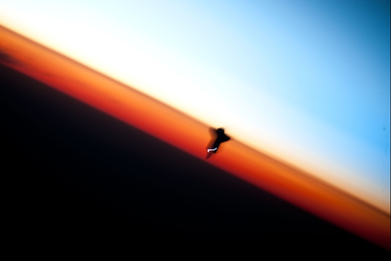 38. Orbital Sunset: Earth's Colorful Horizon and the Silhouette of Space Shuttle Endeavour (STS-130), February 9, 2010, As Seen From the International Space Station (Expedition Twenty-Two) While Orbiting Above the South Pacific Ocean Off the Coast of Southern Chile: Latitude (LAT): -46.9, Longitude (LON): -80.5, Altitude (ALT): 183 Nautical Miles. Photo Credit: STS-130 Shuttle Mission Imagery (http://spaceflight.nasa.gov/gallery/images/shuttle/sts-130/ndxpage1.html), ISS022-E-062675 (http://spaceflight.nasa.gov/gallery/images/shuttle/sts-130/html/iss022e062675.html), NASA Human Space Flight (http://spaceflight.nasa.gov), National Aeronautics and Space Administration (NASA, http://www.nasa.gov), Government of the United States of America. Additional details from NASA: 'The orange layer is the troposphere, where all of the weather and clouds which we typically watch and experience are generated and contained. This orange layer gives way to the whitish Stratosphere and then into the Mesosphere. In some frames the black color is part of a window frame rather than the blackness of space.'