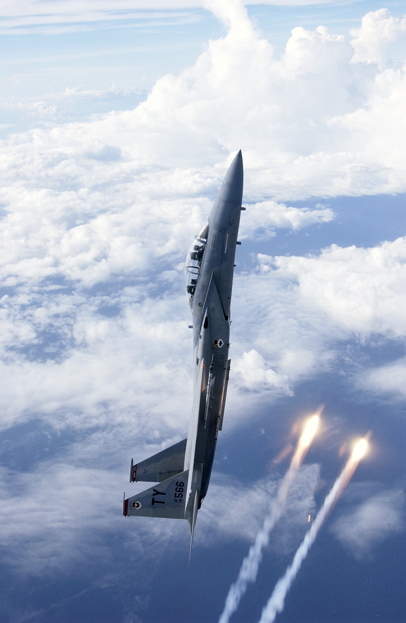 39. A U.S. Air Force F-15D Eagle Fighter Jet In A Vertical Climb Above the Clouds As Flares Streak By. Photo Credit: Staff Sgt. Jeffrey Allen, United States Air Force (USAF, http://www.af.mil, 030814-F-2171A), United States Department of Defense (DoD, http://www.DefenseLink.mil or http://www.dod.gov), Government of the United States of America (USA).