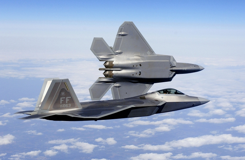 42. New U.S. Air Force F-22A Raptor Stealth Fighter Jets Fly Over the Continental United States of America, March 3, 2006. Photo Credit: Tech. Sgt. Ben Bloker, United States Air Force; Defense Visual Information (DVI, http://www.DefenseImagery.mil, 060303-F-2295B-035 and DF-SD-07-04380) and United States Air Force (USAF, http://www.af.mil), United States Department of Defense (DoD, http://www.DefenseLink.mil or http://www.dod.gov), Government of the United States of America (USA). Full description: 'US Air Force (USAF) Lieutenant Colonel (LTC) Dirk Smith, Commander, 94th Fighter Squadron (FS), peels away from USAF Major (MAJ) Kevin Dolata, Assistant Director of Operations, 94th FS, during the delivery flight of the first F/A-22A Raptor fighters to the 94th FS at Langley Air Force Base (AFB), Virginia (VA). The 94th FS is the second squadron at Langley to receive the new stealth fighter.'