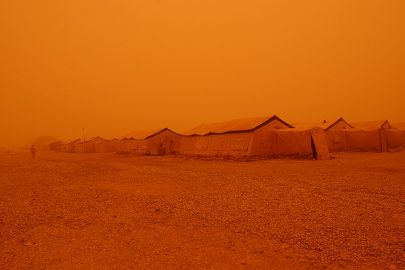 1. The Strong, Dry Desert Wind Blows Huge Clouds of Sand Creating a Hovering Sandstorm Which Changes the Color of the Entire Area, Including the Sky, Into a Surreal Orange Color (Tints of Orange), May 5, 2005, Tallil Air Base, Al Jumhuriyah al Iraqiyah - Republic of Iraq. Photo Credit: Staff Sgt. Darcie Ibidapo, United States Air Force (USAF, http://www.af.mil); DefenseLINK News Photos (http://www.DefenseLink.mil/photos/, 050505-F-4903I-191), United States Department of Defense (DoD, http://www.DefenseLink.mil or http://www.dod.gov), Government of the United States of America (USA).